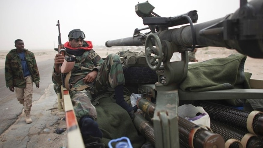 March 4: A defected Libyan soldier sits with his weapons on the outskirts of the eastern town of Brega, Libya.