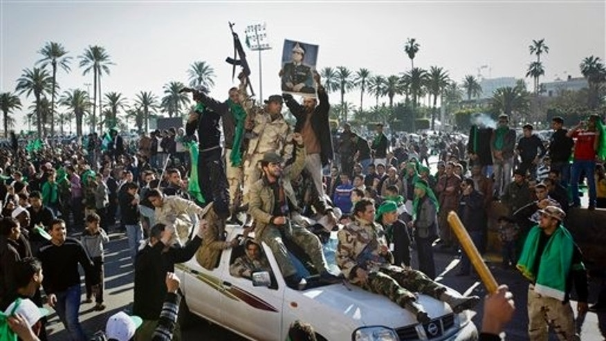 March 6: Pro-Qaddafi soldiers and supporters gather in Green Square in Tripoli, Libya. Thousands of Muammar Qaddafi's supporters poured into the streets of Tripoli on Sunday morning, waving flags and firing their guns in the air in the Libyan leader's main stronghold, claiming overnight military successes. (AP)