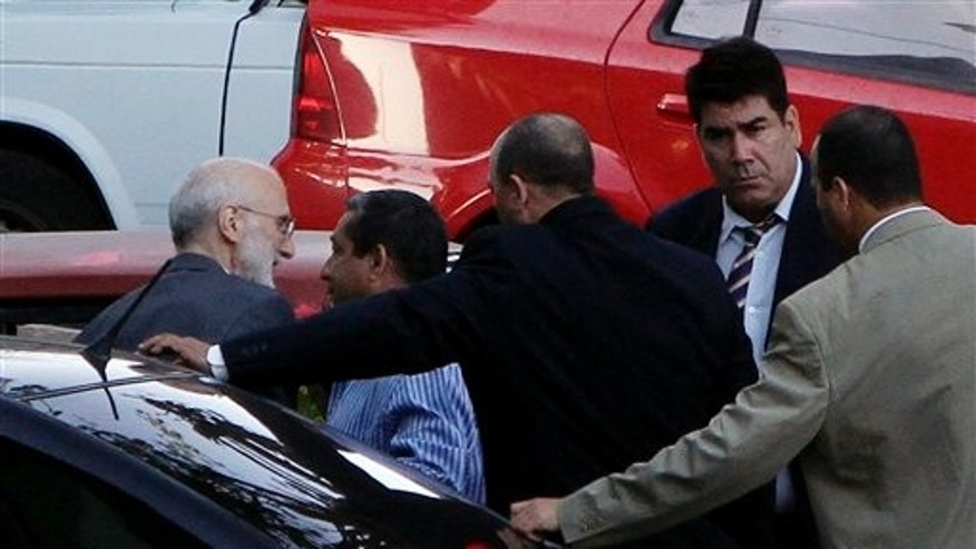 Followed by security  forces members, U.S. government contractor Alan Gross, left, arrives to a courthouse to attend a trial in Havana, Cuba, Saturday March 5, 2011. Gross, a 61-year-old Maryland native, was arrested in December 2009, accused of illegally bringing communications equipment into Cuba for Development Associates International as part of a USAID-backed democracy program. (AP Photo/Franklin Reyes)