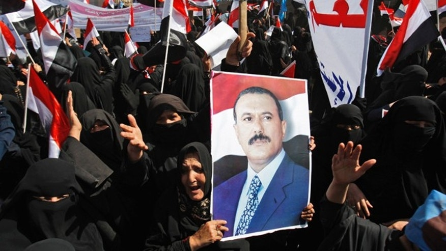 March 5, 2011: Female supporters of Yemeni President Ali Abdullah Saleh raise his portrait and wave their national flag during a rally to support Saleh, in Amran, Yemen. Tens of thousands are continuing with protests in several key cities across Yemen, pressing on with demands that the country's president step down.
