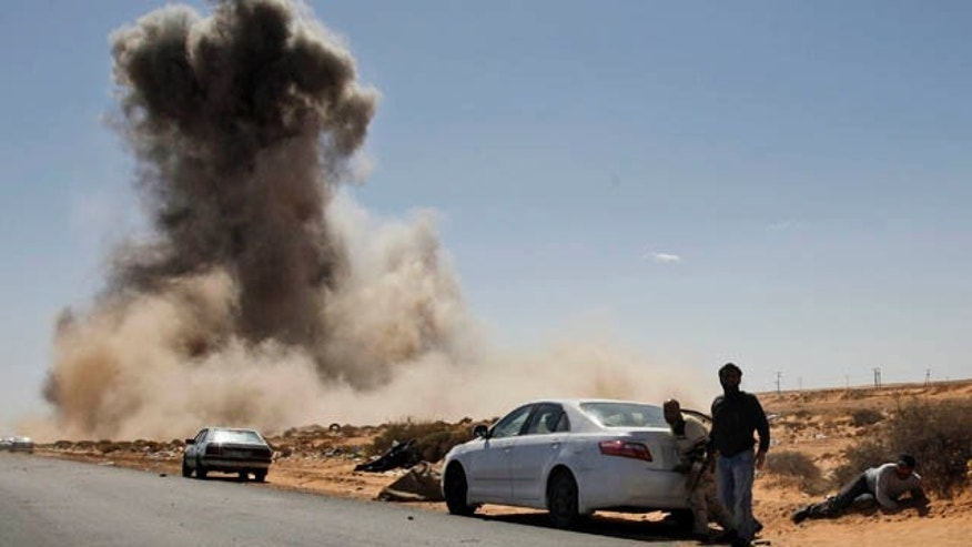 March 7: Smoke raises following an airstrike by Libyan warplanes near a checkpoint close to the anti-Libyan Leader Muammar al-Qaddafi rebels checkpoint in the oil town of Ras Lanouf, eastern Libya. (AP)