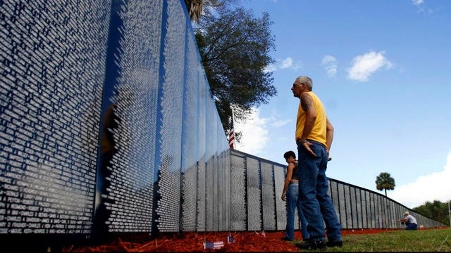 "** ADVANCE FOR USE JULY 4  ** Tony and Marilyn DeMilio, of New Smyrna Beach, Fla., look at the names on the Vietnam Traveling Memorial Wall at Rotary Park in Orange City, Fla., Saturday, June 30, 2007. ""We were out riding and saw the sign,"" Tony DeMilio said. ""I had a lot of friends over there."" A veterans' group based in Michigan, and another, in Florida have both  built replicas of the Vietnam Veterans Memorial in Washington. The groups have fired off volleys of e-mails over a trademark dispute and threatened each other with legal action. (AP Photo/Joe Kaleita)"