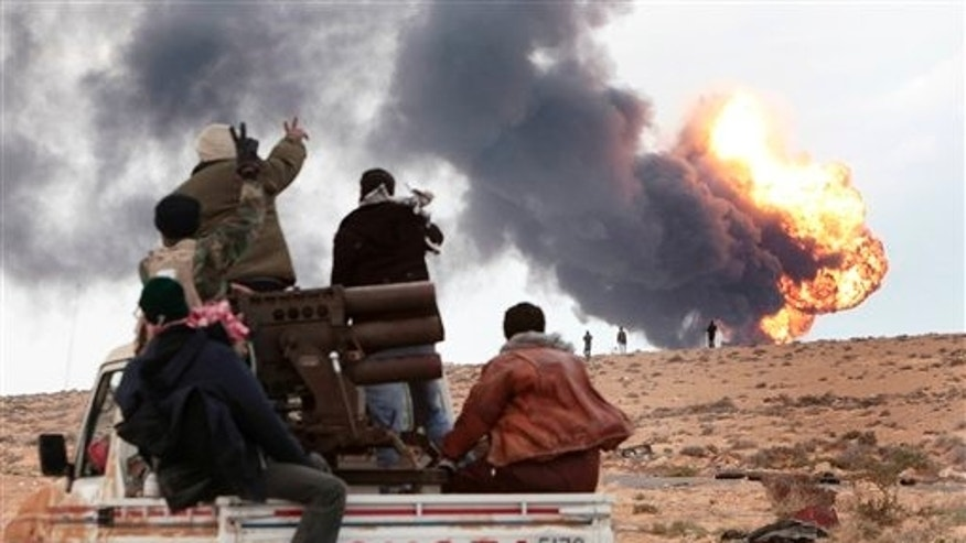 March9: Anti-Qaddafi rebels ride on a truck with a multiple rocket launchers, as flames rises from a fuel storage facility that was attacked during  fighting with pro-fighters, in Sedra, eastern Libya.