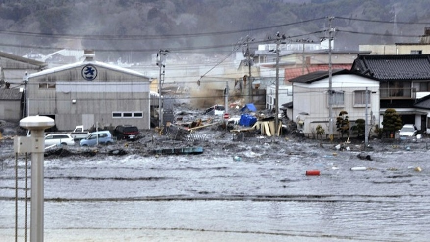 March 11: A tsunami tidal wave washes away houses in Kesennuma, Miyagi Prefecture.