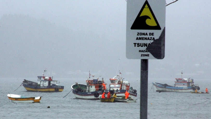 "A sign that reads in Spanish ""Tsunami Risk Zone"" stands along the bay of Dichato, Chile, Friday March 11, 2011.  Latin American governments ordered islanders and coastal residents to head for higher ground on Friday as the Pacific seaboard readied for a possible tsunami raised by Japan's magnitude-8.9 earthquake.  (AP Photo/Mauro Moreno)"
