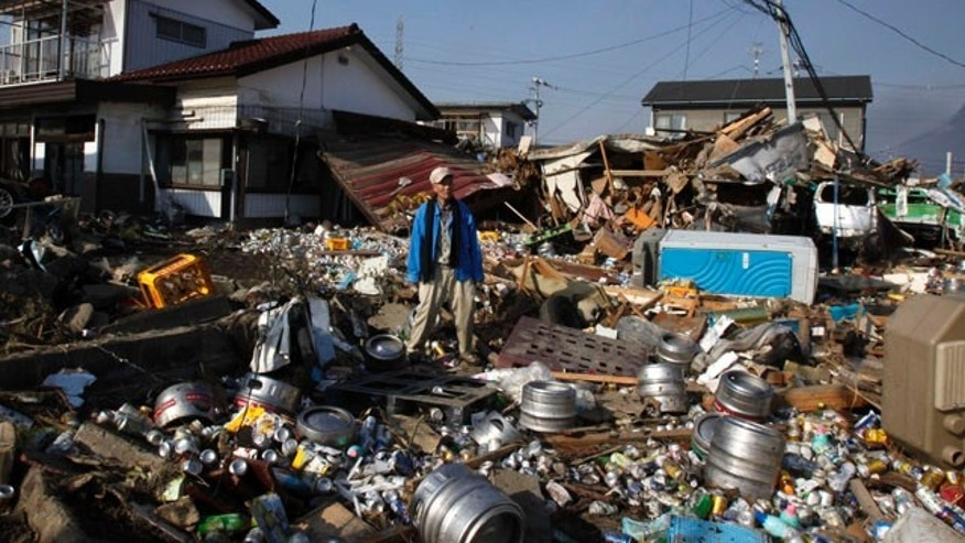 March 13, 2011: A tsunami survivor  stands on debris of houses and beer cans and barrels washed away from a nearby brewery factory after the area was hit by Friday's catastrophic earthquake-triggered tsunami in Sendai in Miyagi Prefecture, northern Japan.