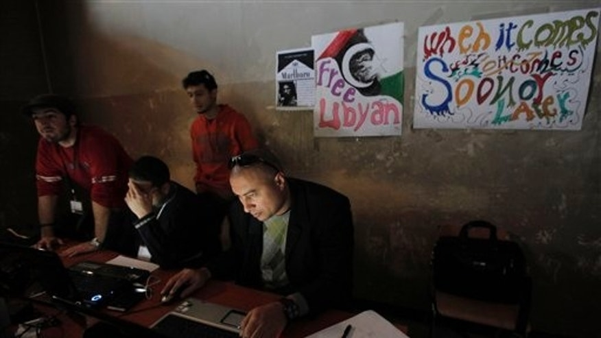 March 7:In this file photo, Libyan volunteers operate at the newly setup media center in what used to be a court house in Benghazi, Libya . The burnt-out building that once housed the high court has been transformed in the past three weeks into a bustling hub of civic life, home to a daily newspaper, a recording studio and a press center. (AP)