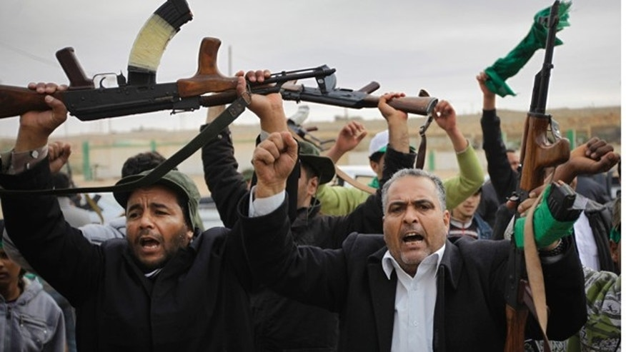 March 12, 2011: Pro-Qaddafi fighters raise their weapons as they are pictured during a government-organized visit for foreign media in Bin Jawwad, 350 miles southeast of the capital Tripoli, in Libya. The world moved a step closer to a decision on imposing a no-fly zone over Libya but Qaddafi was swiftly advancing Saturday on the poorly equipped and loosely organized rebels who have seized much of the country.