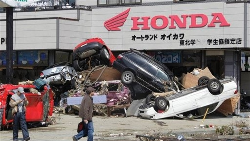 March 13: Men walk by damaged vehicles following a massive tsunami that's triggered by a catastrophic earthquake in Tagajo near Sendai, northeastern Japan. (AP)