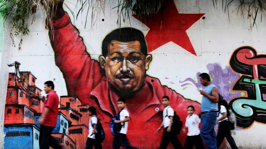 People pass in front a mural depicting Venezuela's President Hugo Chavez in Caracas, Venezuela, Wednesday, Feb. 2, 2011. Chavez celebrated his 12th anniversary in power Wednesday saying he is ready to battle for six more years in next year's election. (AP Photo/Ariana Cubillos)