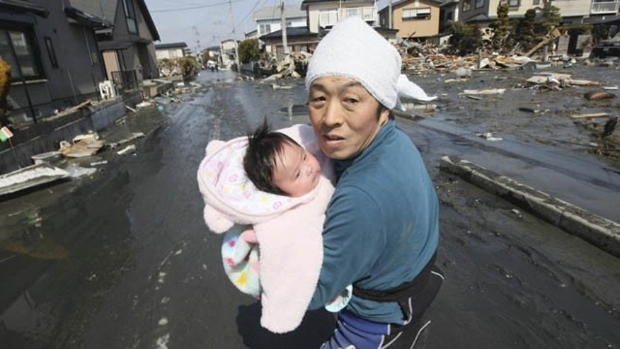 March 14: Upon hearing another tsunami warning, a father tries to flee for safety with his just reunited four-month-old baby girl who was spotted by Japan's Self-Defense Force member in the rubble of tsunami-torn Ishinomaki Monday, three days after a powerful earthquake-triggered tsunami hit northeast Japan. (AP)