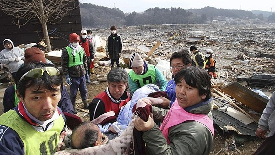 March 14: Rescue workers carry an elderly man found alive by tsunami survivors buried under rubble along a slope of a hill in n Minami Sanrikucho in Iwate Prefecture three days after a powerful earthquake-triggered tsunami hit the country's east coast.