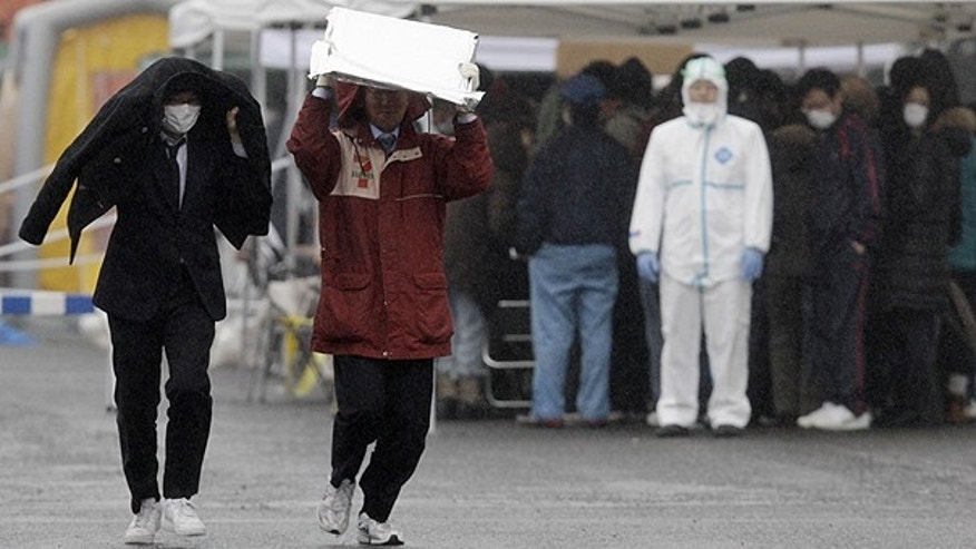 March 15: People carry heat blankets as they leave a radiation emergency scanning center in the raun in Koriyama, Fukushima Prefecture, Japan, four days after a giant quake and tsunami struck the country's northeastern coast.