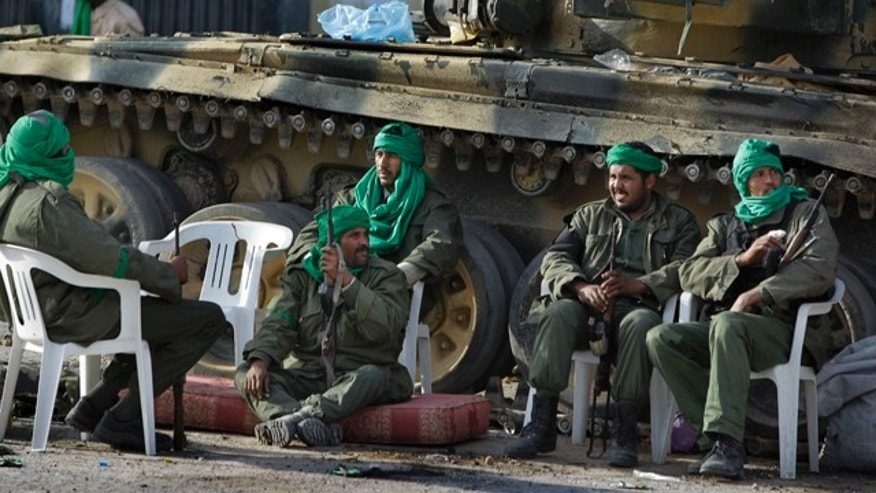 March 11: In this photo taken during a government organized visit for foreign media, pro-Qaddafi soldiers sit by their tank next to a destroyed building in the main square of Zawiya.