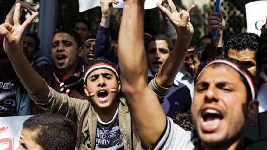 March 12: People shout slogans as they protest outside the Arab League headquarters in Cairo, Egypt, to urge Arab foreign ministers meeting to approve a no-fly zone over Libya to protect the civilian population from Libyan leader Muammar Qaddafi's fighter jets. (AP)