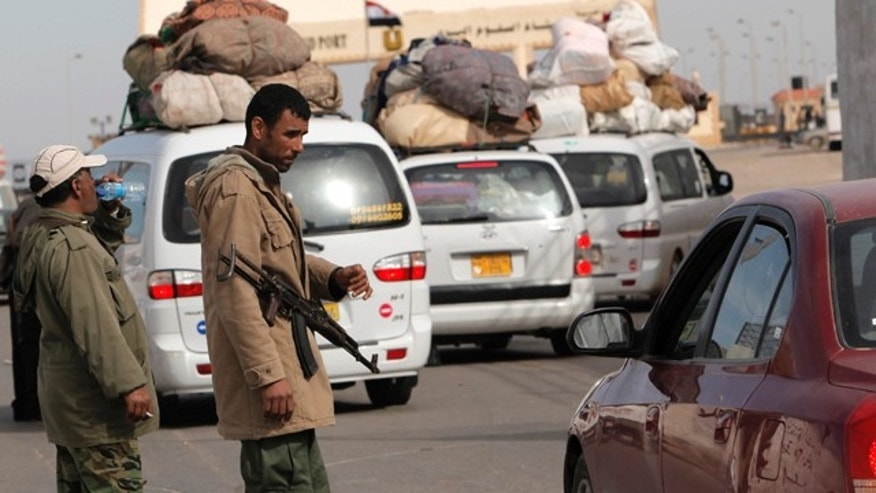 March 16: Two Libyan rebels check vehicles crossing toward Egypt at the Libyan terminal of the Egyptian Libyan border crossing near the border town of Musaed, Libya.