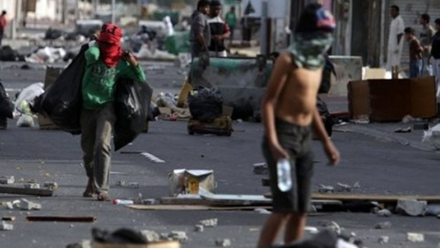 March 16: Shiite Bahraini youths haul debris into the streets of the western village of Malkiya, Bahrain, in preparation for government-supporting forces they anticipate will roll into their Shiite Muslim village southwest of the capital of Manama.