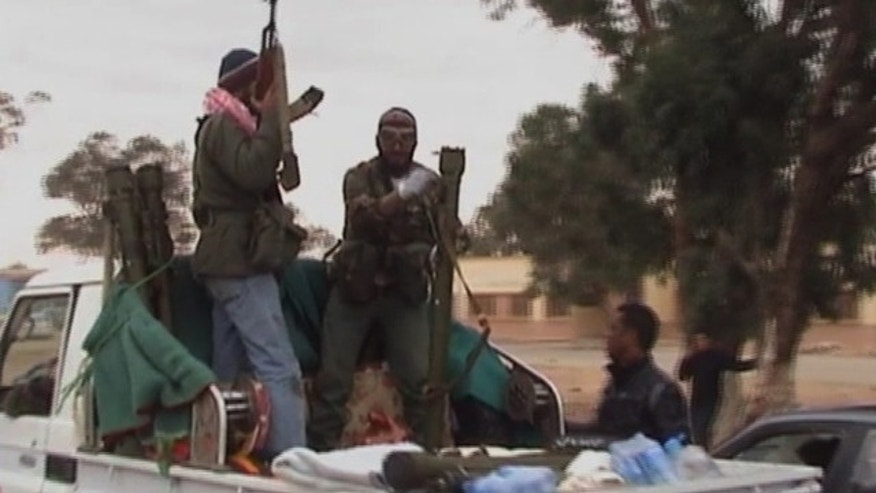 March 17, 2011: Rebels hold on to the back of a vehicle in the area of Benina, a civilian and military airport, outside Benghazi in eastern Libya