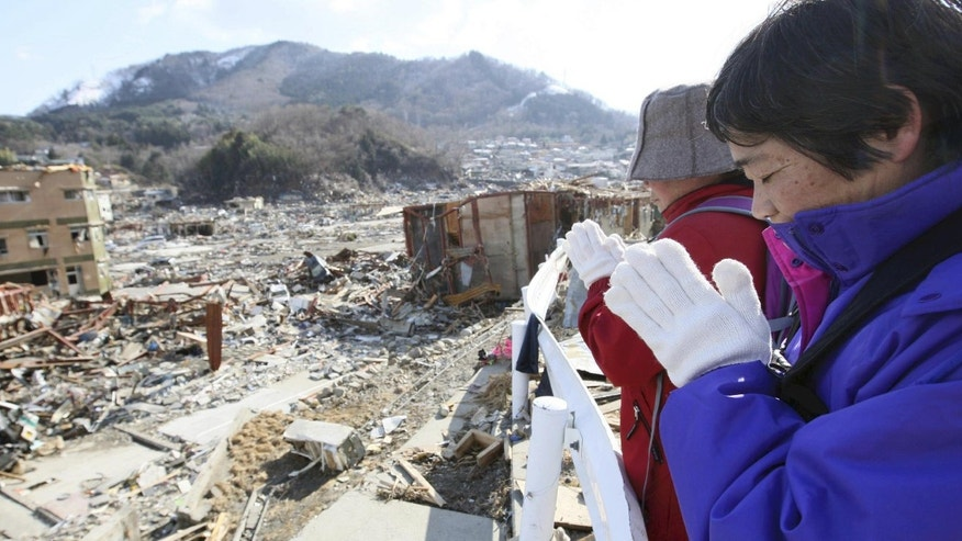 Survivors press their hands together in prayer to mourn their relatives at the devastated town of Onagawa, northeastern Japan, on Friday, March 18, 2011, just one week after a massive earthquake and resulting tsunami.