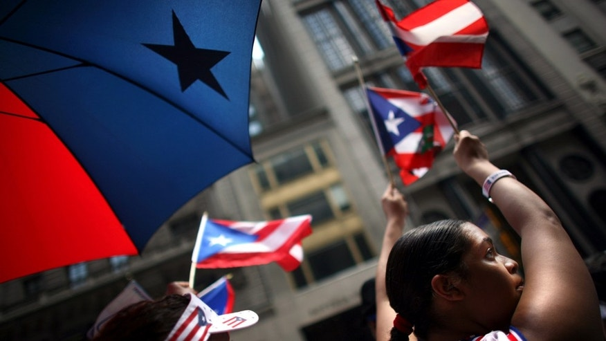 NEW YORK CITY - JUNE 8:  An attendant cheers in the annual Puerto Rico Day Parade June 8, 2008 in New York City. The parade honoring Puerto Ricans is an annual New York City tradition and takes place along Fifth Avenue.  (Photo by Yana Paskova/Getty Images)