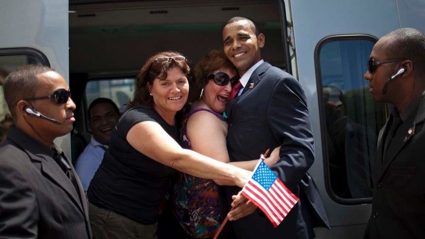 Rinaldo Americo, an impersonator of President Barack Obama, second from right, poses for photos with tourists who stopped their van to greet him, as two men impersonate his security detail in Cinelandia Square where the real President Obama will be giving a speech in Rio de Janeiro, Brazil, Wednesday March 16, 2011.  Obama is scheduled to visit Brazil on March 19 and 20 as part of a Latin American tour that also includes Chile and El Salvador. (AP Photo/Felipe Dana)