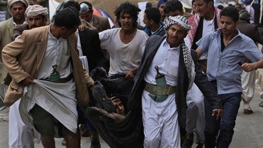 March 18: Anti-government protestors carry a wounded protestor in a blanket from the site of clashes with security forces in Sanaa, Yemen.