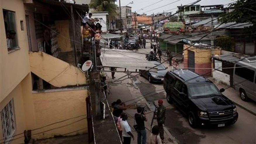 President Barack Obama, into a vehicle, bottom right, arrives in the slum Cidade de Deus, or City of God,  in Rio de Janeiro, Brazil, Sunday, March 20, 2011. Obama arrived in Brazil on Saturday for the start of a three-country, five-day tour of Latin America. (AP Photo/Felipe Dana))