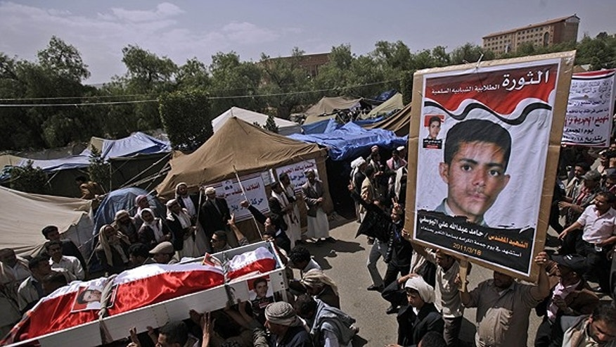 March 20: Anti-government protestors carry the body of Hamid Ali, his poster seen right, who was killed on Friday's clashes with Yemeni security forces, during his funeral procession in Sanaa.