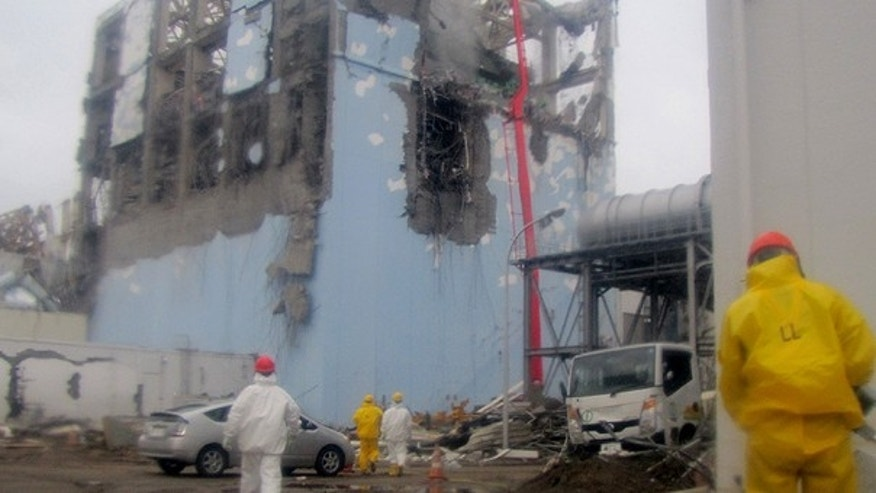 March 22: In this photo released by Tokyo Electric Power Co. (TEPCO) , workers in protective suits conduct cooling operation by spraying water at the damaged No. 4 unit of the Fukushima Dai-ichi nuclear complex in Okumamachi, northeastern Japan.
