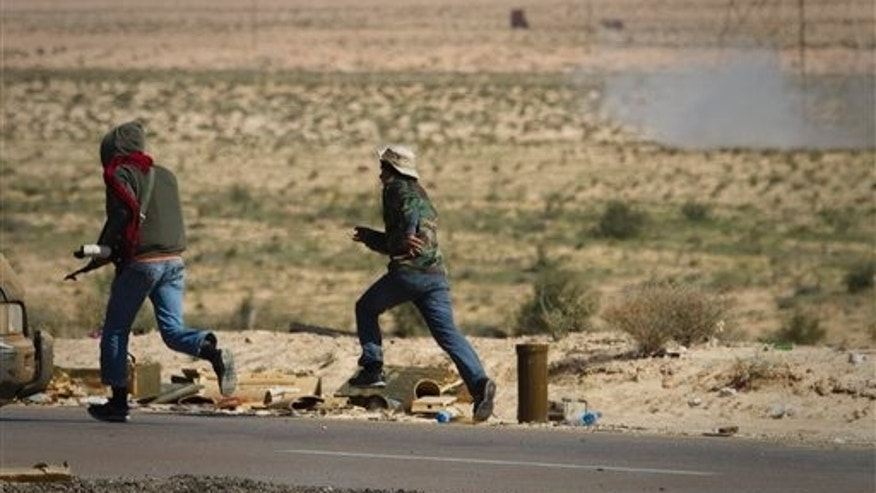 March 22: Libyan rebels run to take cover as a mortar, seen at top right, from Muammar al-Qaddafi's forces are fired on them on the frontline of the outskirts of the city of Ajdabiya, south of Benghazi, eastern Libya.