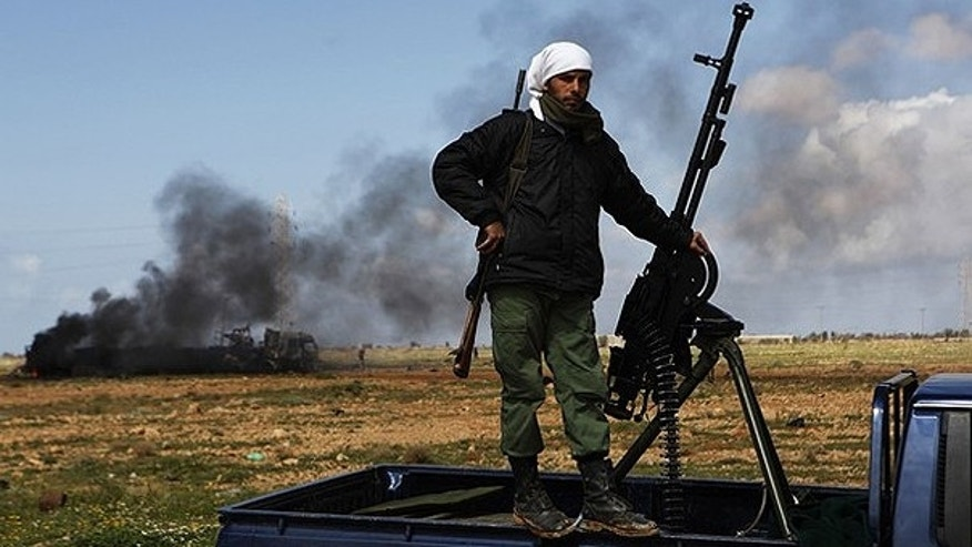 March 20: A rebel fighter stands beside his weapon at the scene of what residents said was a French airstrike against Muammar Gaddafi's forces on the southern outskirts of Benghazi in northeastern Libya.