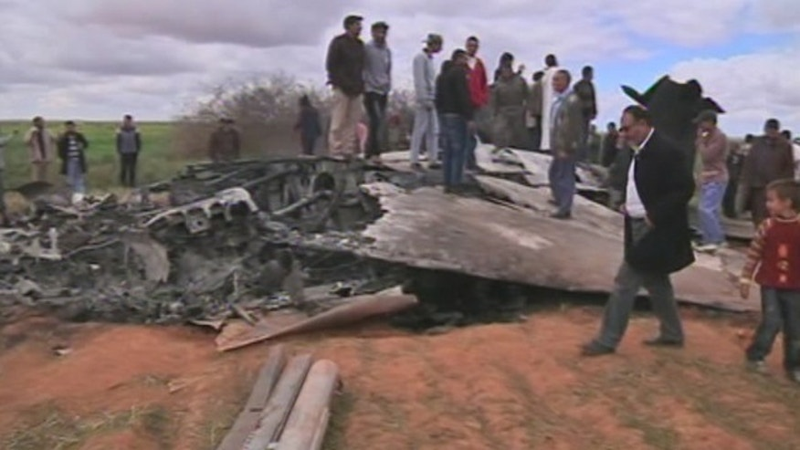 March 22: Libyans stand over wreckage from a downed U.S. F-15 fighter jet.