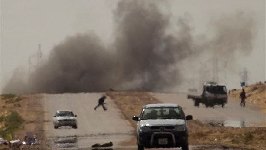 March 22: Libyan rebels try to take cover as mortars from Muammar al-Qaddafi's forces are fired on them on the frontline of the outskirts of the city of Ajdabiya, south of Benghazi, eastern Libya.