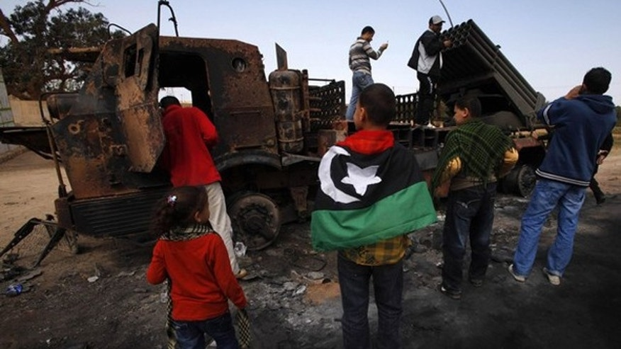 March 23: People look at weapons belonging to forces loyal to Libyan leader Muammar al-Qaddafi, destroyed by a coalition air strike, along a road between Benghazi and Ajdabiyah.