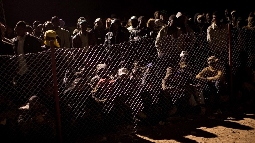 March 20: Men from Ghana, who used to work in Libya and fled the unrest in the country, are seen behind a fence as they wait for news regarding their repatriation process after crossing from Libya in a refugee camp at the Tunisia-Libya border, in Ras Ajdir, Tunisia. More than 250,000 migrant workers have left Libya for neighboring countries, primarily Tunisia and Egypt, in the past three weeks.