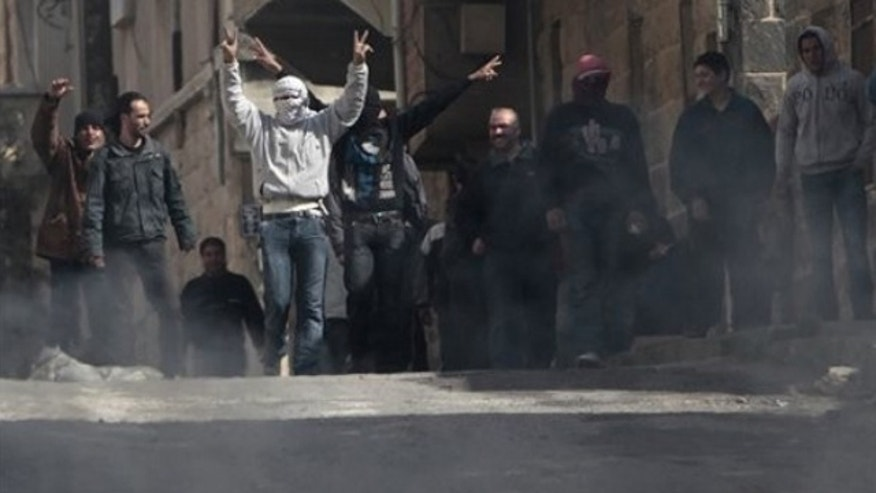 March 23: Anti-Syrian government protesters flash V sign as they protest in the southern city of Daraa, Syria.