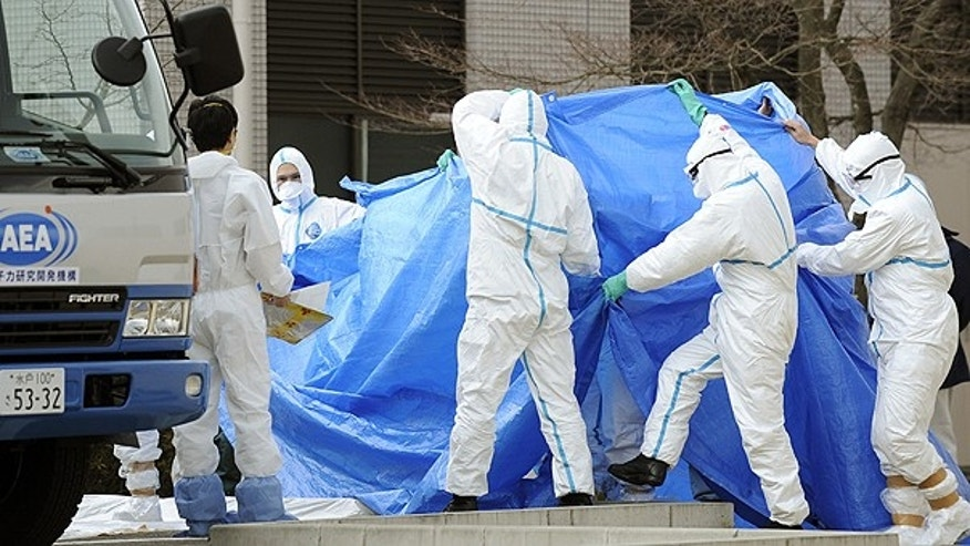 March 25: Workers, who stepped into radiation-contaminated water during Thursday's operation at the Fukushima Dai-ichi nuclear plant, are shielded with tarps before receiving decontamination treatment at a hospital in Fukushima, northeastern Japan.