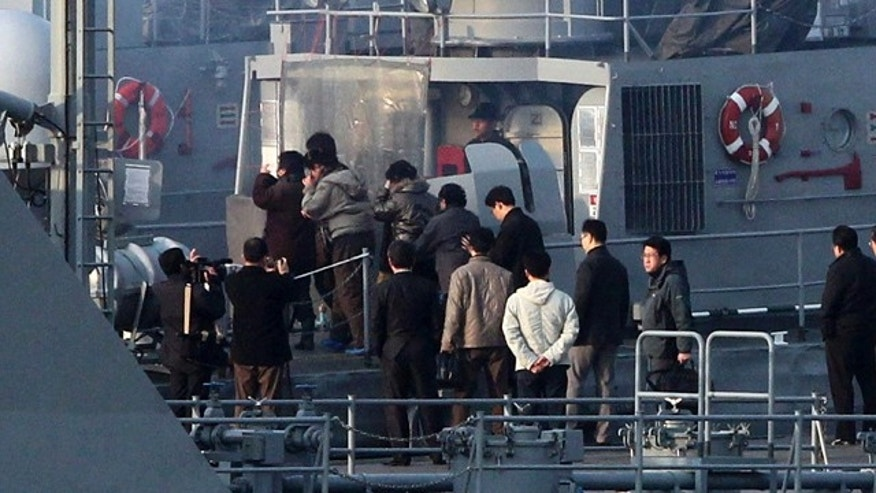 March 27, 2011: North Koreans board a South Korean navy ship to return the North at a port in Incheon, South Korea.