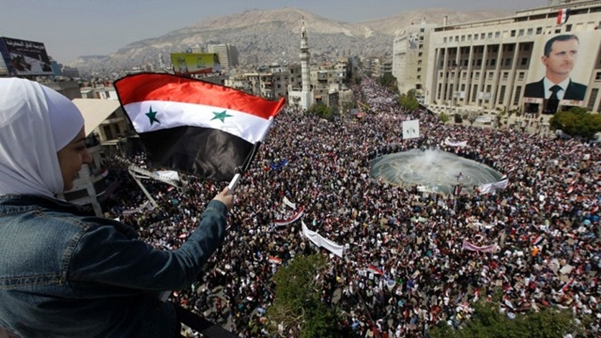 Pro-Syrian President Bashar Assad protester, waves Syrian flag as she looks to the crowed who demonstarte to show their support for their president, in Damascus, Syria, on Tuesday March 29, 2011. Pledging allegiance for President Bashar Assad as he faces the biggest challenge to his 11-year rule, hundreds of thousands of Syrians gathered in a central Damascus square Tuesday, waving his pictures and chanting support. (AP Photo/Bassem Tellawi)