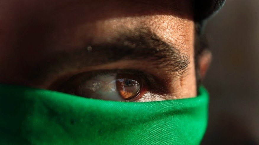 March 29: A pro Gadhafi supporter wears a green scarf on his face in Tripoli, Libya.