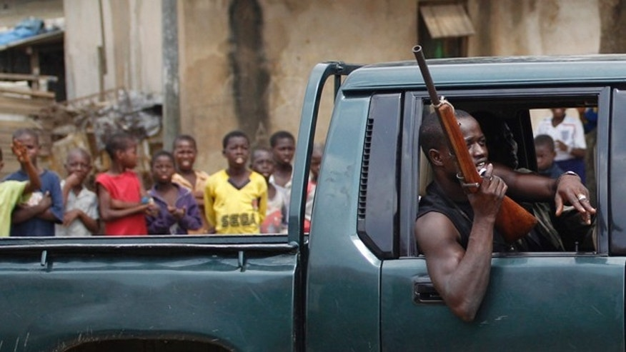 March 12: Children look on as a fighter opposed to Laurent Gbagbo passes in a pick-up truck, in the Anyama neighborhood of Abidjan, Ivory Coast