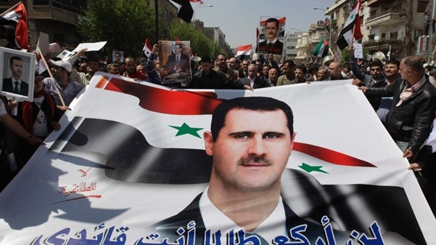 """March 29: Pro-Syrian President Bashar Assad supporters hold Assad's poster with Arabic words reading: """"I'll not kneel as long as you are my leader"""" as they demonstrate to show their support for their president, in Damascus, Syria."""
