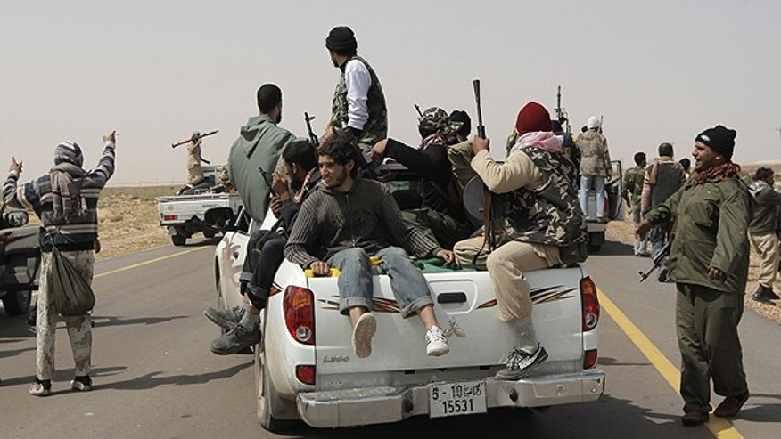 March 30: Libyan rebels ride at the back of a pickup truck while retreating back east, at the outskirts of the town of al-Agila, Libya.