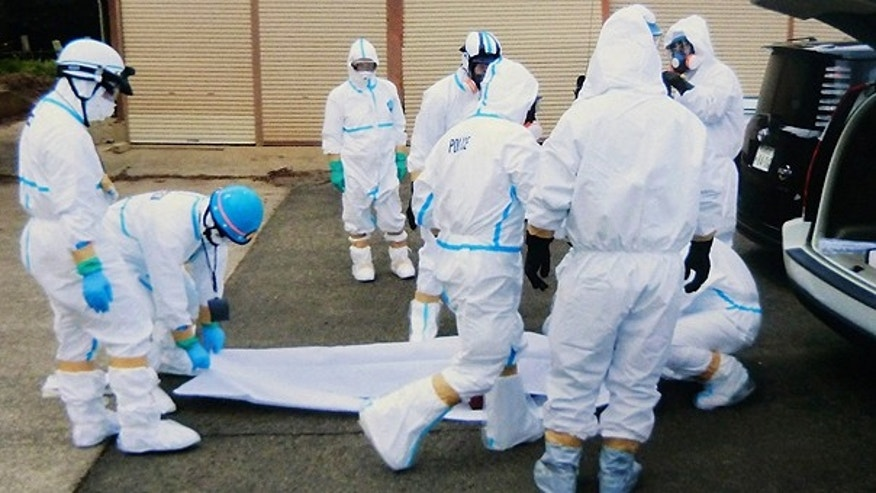 March 27: Police officers in protective suits surround a body found following the March 11 earthquake within 5 kilometers from the crippled Fukushima Dai-Ichi nuclear plant in Okumamachi, Fukushima Prefecture, northern Japan.
