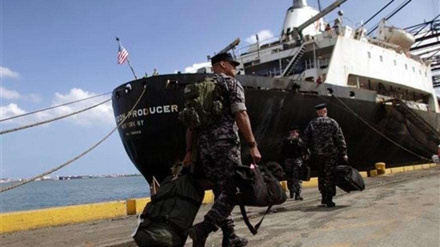 April 1, 2011: Private security officers from the International Maritime Security Network company walk to U.S. cargo vessel Horizon Producer for an anti-piracy security demonstration in Puerto Rico.