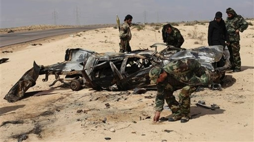 April 2: A Libyan rebel collects the charred remains of rebels who were allegedly killed in NATO coalition airstrike overnight, as others inspect the damaged vehicle along the front line near Brega, Libya. NATO said on Saturday that it was investigating Libyan rebel reports that a coalition warplane had struck a rebel position that was firing into the air near the eastern front line of the battle with Qaddafi's forces. (AP)