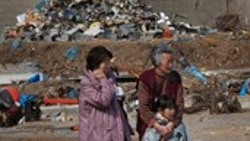 March 31: Survivors watch workers finding victims at the tsunami-destroyed town of Yamada, Iwate Prefecture, northern Japan.