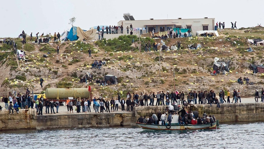 Migrants on a boat approach the Lampedusa harbor, Italy, Monday, March 28, 2011. Fishermen have used empty migrants' boats to block the entrance to Lampedusa harbor, a mostly symbolic act which still raised cheers from townsfolk gathered on the quays. News reports Monday said the boats, which had been seized by Italian authorities, were used to block the tiny island's port. Officials reported 460 migrants arrived from North Africa overnight, joining 3,000 more who have arrived in the last three days and escalating tensions on the island, closer to Africa than to mainland Italy.