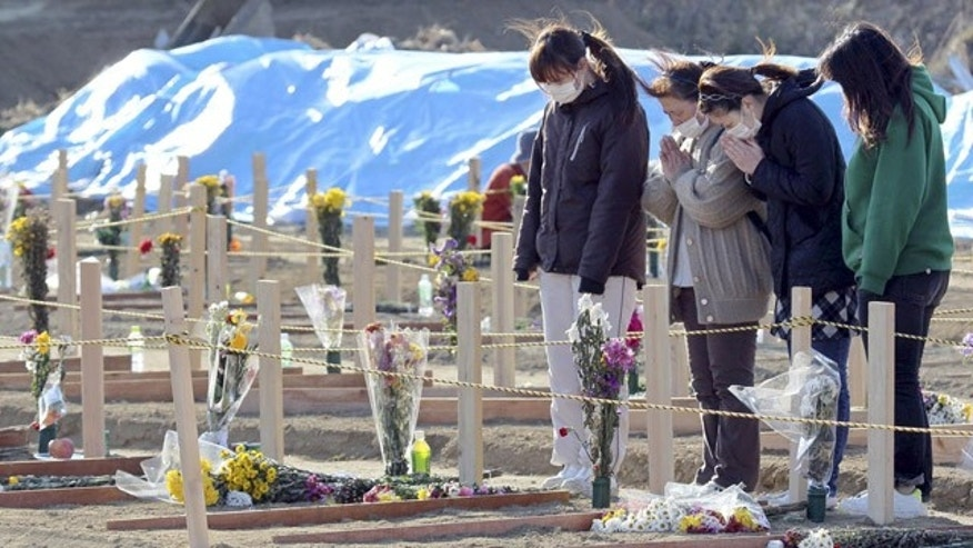 April 3, 2011: Survivors offer a prayer at the site where coffins of victims of the March 11 earthquake and tsunami were buried in Higashimatsushima, Miyagi Prefecture, Japan.