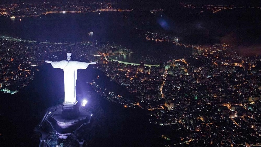 "An aerial view of the iconic Christ the Redeemer statue before the lights that illuminate the statue are switched off to observe an hour of voluntary darkness for the global ""Earth Hour"" campaign, in Rio de Janeiro, Brazil, Saturday March 26, 2011.  An estimated 1,000 landmarks' lights were turned off worldwide for 60 minutes at 8:30 p.m. local time, as a symbolic act to raise awareness about climate change and to make people aware of everyday energy use.  (AP Photo/Felipe Dana)"